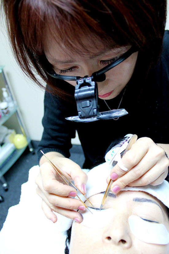 A woman is doing permanent makeup.