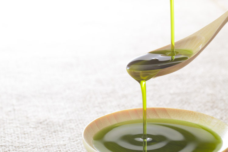 Green liquid with a wooden spoon and a small plate.