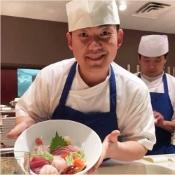 Sushi chief with bowl of sashimi.