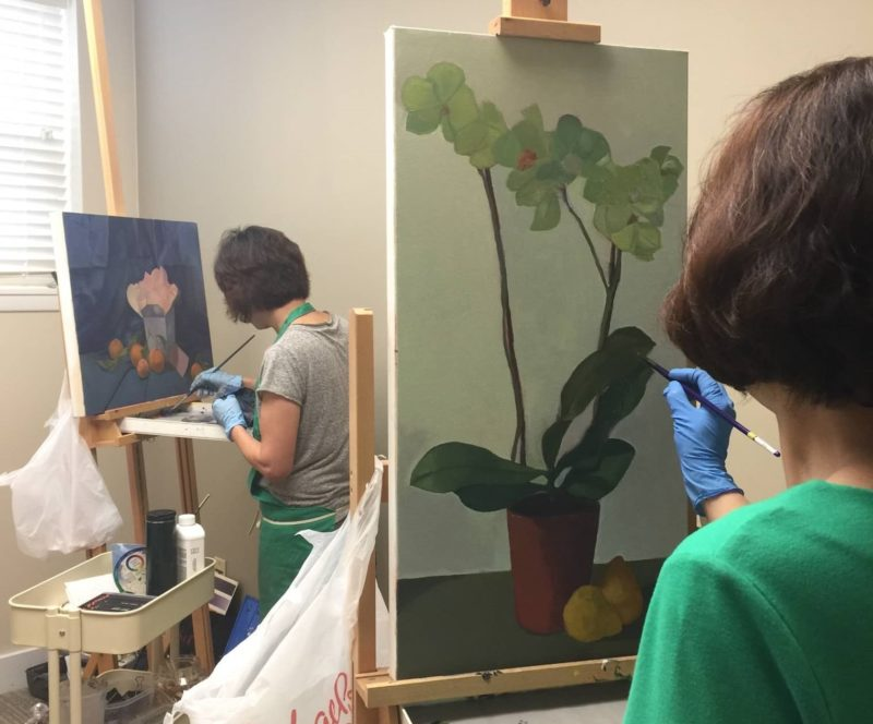 women are painting oil paint.